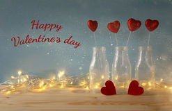Glitter hearts in the glass vases on wooden table. Valentines day background. Glitter hearts in the glass vases on wooden table royalty free stock images
