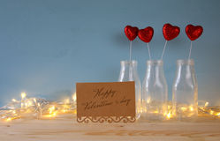 Glitter hearts in the glass vases on wooden table. Valentines day background. Glitter hearts in the glass vases on wooden table royalty free stock photo