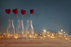 Glitter hearts in the glass vases on wooden table. Valentines day background. Glitter hearts in the glass vases on wooden table. Filtered and toned image stock images