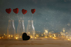 Glitter hearts in the glass vases on wooden table. Valentines day background. Glitter hearts in the glass vases on wooden table. Filtered and toned image royalty free stock image