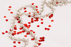 Glitter hearts and pearls. Red glitter hearts on a white background with pearls Stock Images