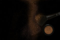 Glitter make up brush and powder dust on black background Royalty Free Stock Images
