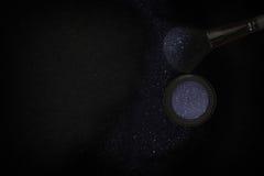 Glitter make up brush and powder dust on black background Stock Image