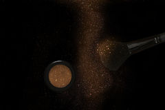 Glitter make up brush and powder dust on black background Stock Images