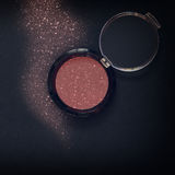 Glitter make up powder dust on black background Royalty Free Stock Images