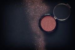 Glitter make up powder dust on black background Stock Photo