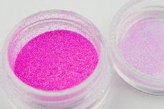 Glitter for nail art. Opened container of pink glitter for nail art Royalty Free Stock Photo