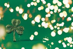 Glitter shamrock on green paper background. St Patricks day symbol. Irish National holiday concept. Bold festive bokeh. Glitter shamrock on green paper royalty free stock images