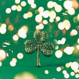 Glitter shamrock on green paper background. St Patricks day symbol. Irish National holiday concept. Bold festive bokeh. Glitter shamrock on green paper royalty free stock photo