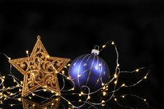 Glitter star and bauble with lights. Gold glitter Christmas star and blue and silver bauble surrounded by fairy lights against black royalty free stock photography