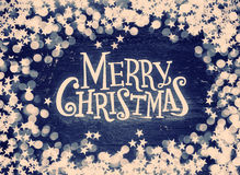 Glitter stars and defocused lights on grunge wood with Merry Christmas text. Retro tinted Stock Photo
