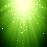 Glitter stars descending on green light burst. An abstract sparkling stars descending on green light burst background Royalty Free Stock Photography