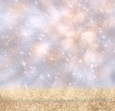 Glitter vintage lights background. gold, silver, and white. de-focused. royalty free stock image