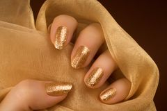 Glittered golden nails manicure. Female hand with glittered golden nails is holding a golden luxury textile material on brown background Royalty Free Stock Photos