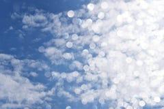 Glittering bokeh circular white on blue sky background. Royalty Free Stock Image
