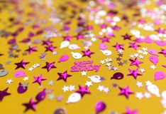 Glittering confetti on yellow background royalty free stock images