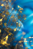 Glittering Fabric. Blue and gold glittering fabric, close up royalty free stock photography