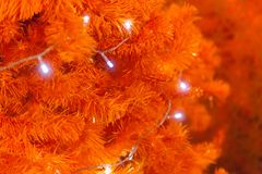 Glittering and Glowing Sparkling white defocused Light bokeh Illumination orange background with decorated Christmas Tree. Special Holidays, Festival design royalty free stock images