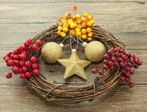 Glittering gold Christmas balls, bells,wreath, and star on wooden background with snow . Stock Images