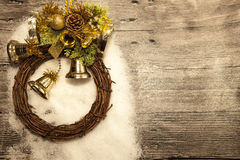 Glittering gold Christmas balls, bells,wreath, and star on wooden background with snow . Royalty Free Stock Photo
