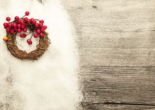 Glittering gold Christmas balls, bells,wreath, and star on wooden background with snow . Royalty Free Stock Photos