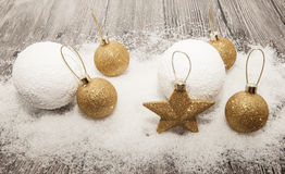Glittering gold Christmas balls, snowballs, winter snow and star on wooden background Royalty Free Stock Photo