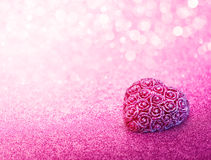 Glittering Heart Shaped on Pink Background Stock Photo