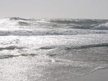 Glittering waves beneath pale sky Stock Image