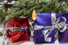 Christmas presents under the Christmas tree. Glittering wrapped Christmas presents under the Christmas tree - closeup of small package stock photos