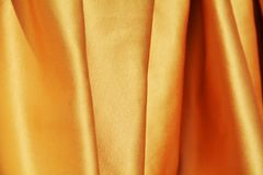 Glittery folds, background. The glittery golden folds of the soft elegant fabric suggest the abundance and luxury, joy and serenity. Background Stock Photography
