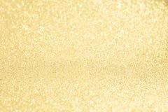 Glittery glänzender Lichtgoldzusammenfassungshintergrund Stockfoto