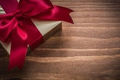 Glittery Gold-giftbox mit rotem Band auf hölzernem Brett der Weinlese Lizenzfreie Stockfotografie