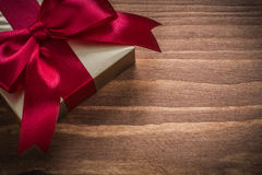 Glittery gold giftbox with red ribbon on vintage wooden board Royalty Free Stock Photography