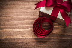 Glittery Goldgeschenkbox rollte Band auf hölzernem Brett der Weinlese Lizenzfreies Stockbild
