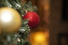 Glittery red christmas tree ornament. Glittery red christmas ornament on tree with a warm, orange bokeh light in the background royalty free stock photos