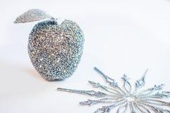 Glittery silberner Apfel und eine Schneeflocke auf einem weißen Hintergrund Lizenzfreies Stockbild