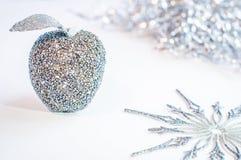 Glittery silberner Apfel und eine Schneeflocke auf einem weißen Hintergrund Stockfotografie