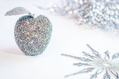 Glittery silver apple and a snowflake on a white background. Stock Photography