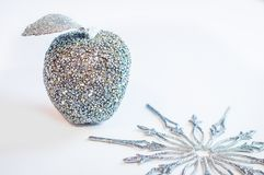Glittery silver apple and a snowflake on a white background. Royalty Free Stock Image