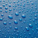 Glittra vattensmå droppar på vaxad blåttmetall royaltyfria bilder