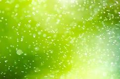 Glitzernde Tropfen des unscharfen Hintergrundes des Sprays Sonnenaufgang Lizenzfreie Stockfotografie