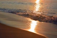 Glitzernde und goldene Wellen bei Sonnenaufgang Lizenzfreies Stockbild