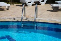Glänzende Chromleiter im Pool mit blauem Wasser Stockfotos