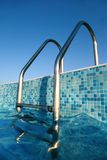 Glänzende Chromstrichleiter in Pool, blauer Himmel Stockbild