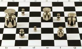 Glänzende Stahlgewichte der Skala auf Schachbrettoberfläche Stockfotografie