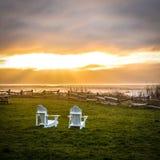 Glänzender Sonnenuntergang über Ozean mit Stühlen Stockbild