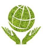 Glob με τη μορφή χεριών στην πράσινη χλόη στοκ εικόνα