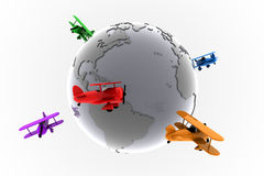 Global aviation with toy planes. Toy airplanes around a metal globe of earth demonstrate global aviation Royalty Free Stock Photography