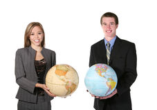 Global Business. A young man and woman holding globes against a white background royalty free stock images