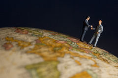 Global business. Business figurines one earth globe shaking hands Stock Photo